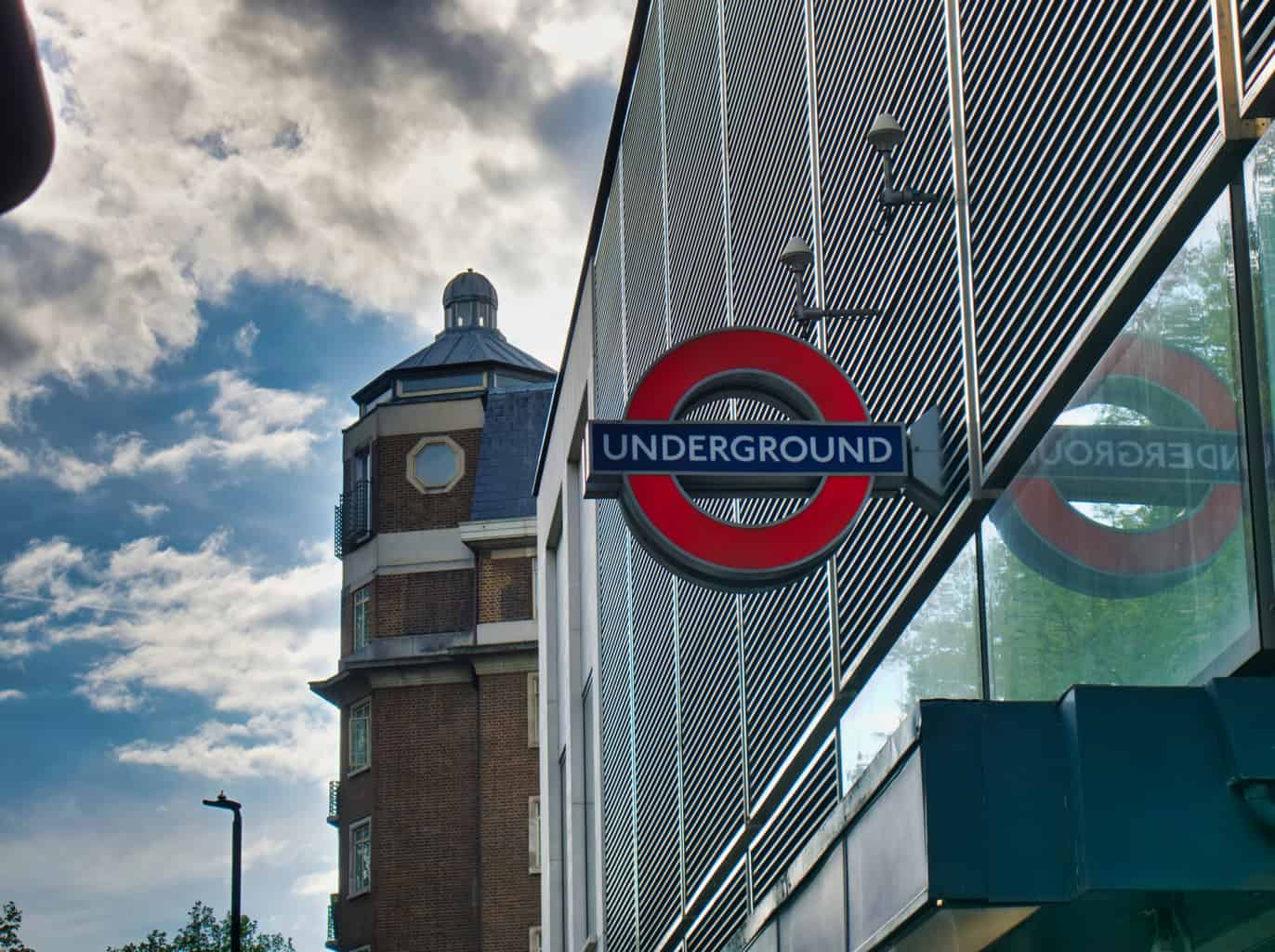A London Undergound sign with ominous clouds and a building behind