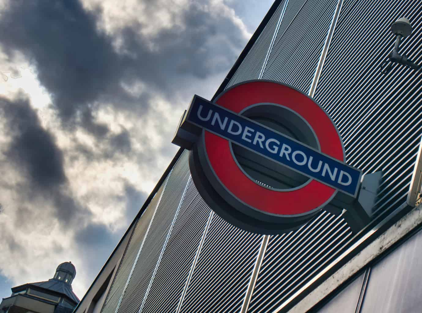A close shot of a London Undergound sign with ominous clouds behind