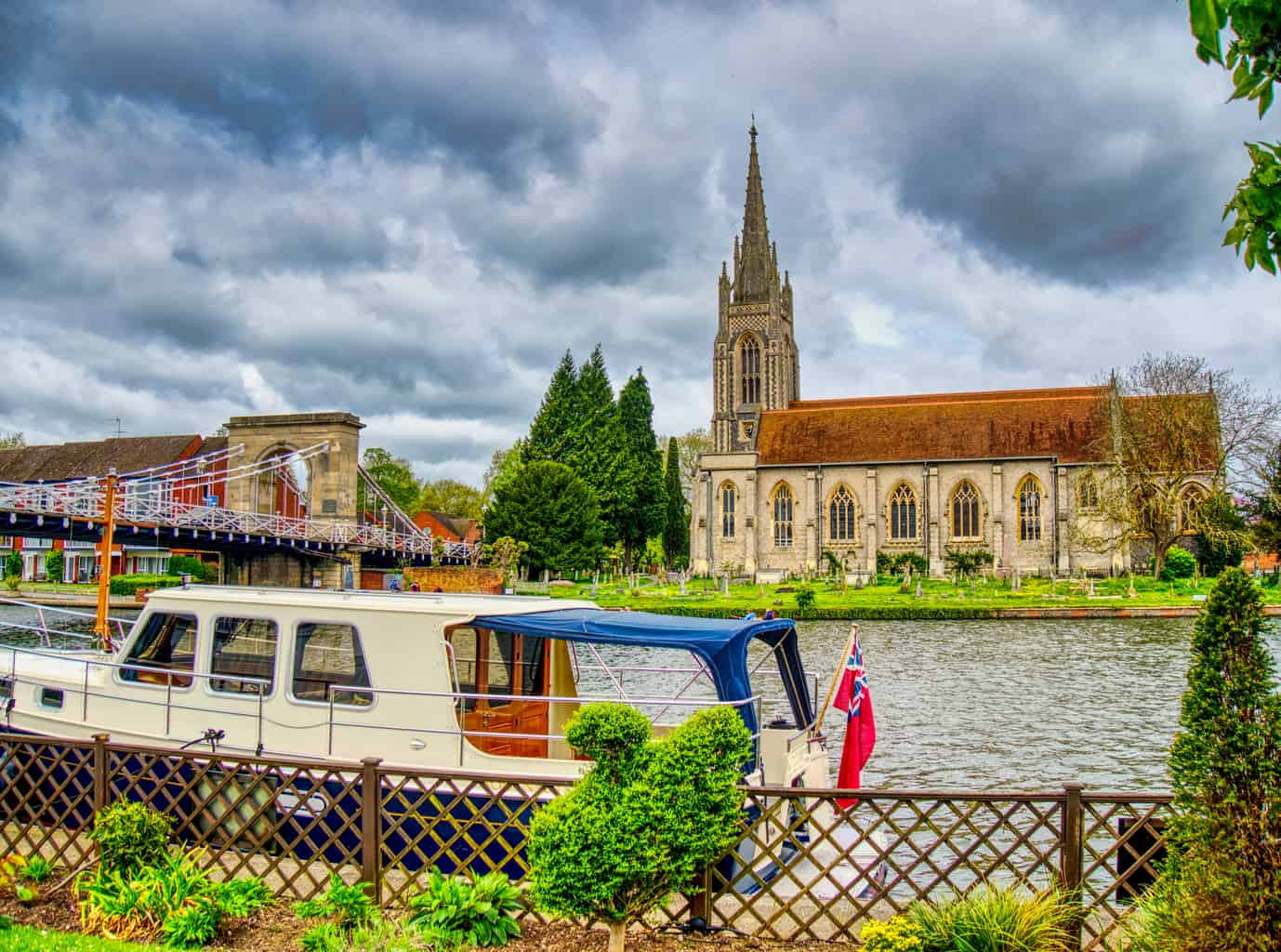 A boat on a river in Marlow with a church behind with dark clouds and green trees