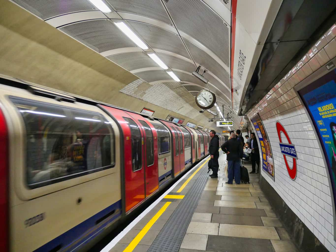 A London Underground train waiting at Lancaster Gate with people waiting to get on