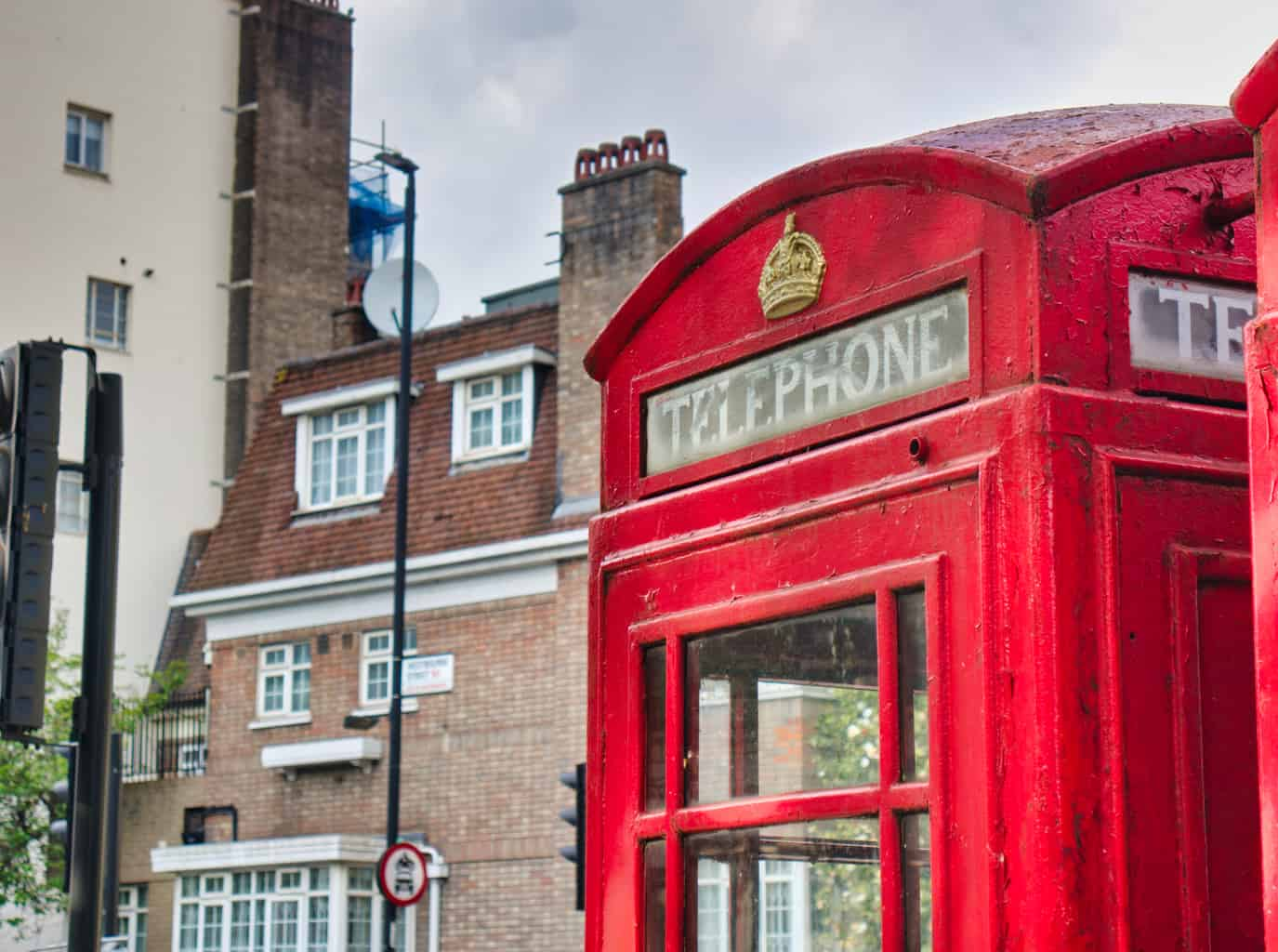 A red telephone booth in London with a building behind