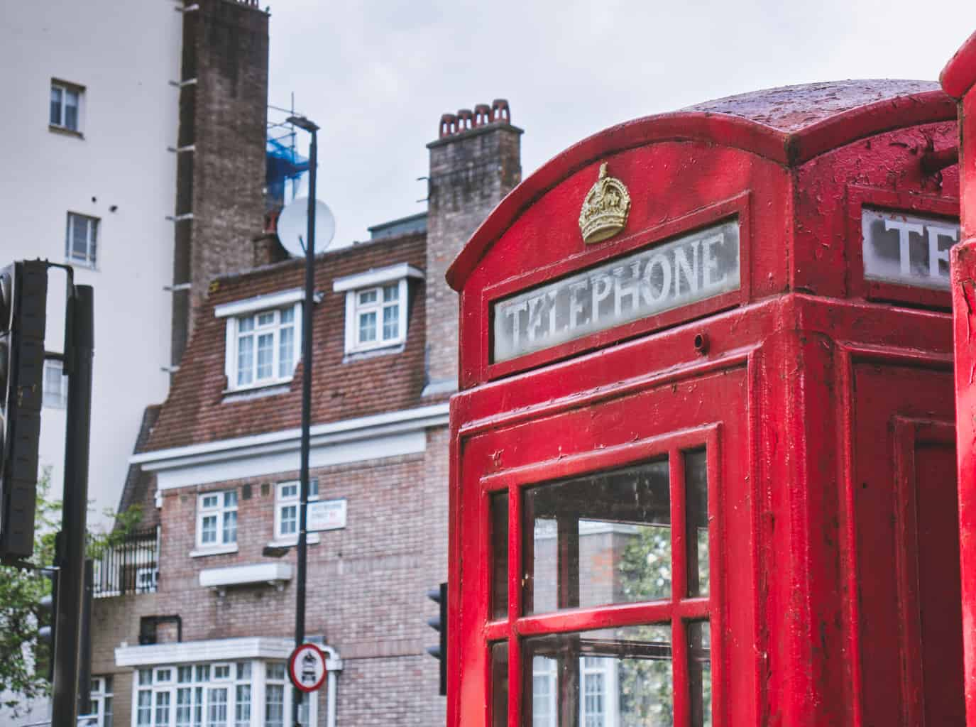 A red telephone booth in London with a building behind with muted colours