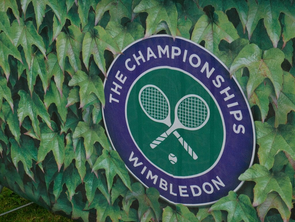 The Wimbledon logo surrounded by leaves printed on an advertising board