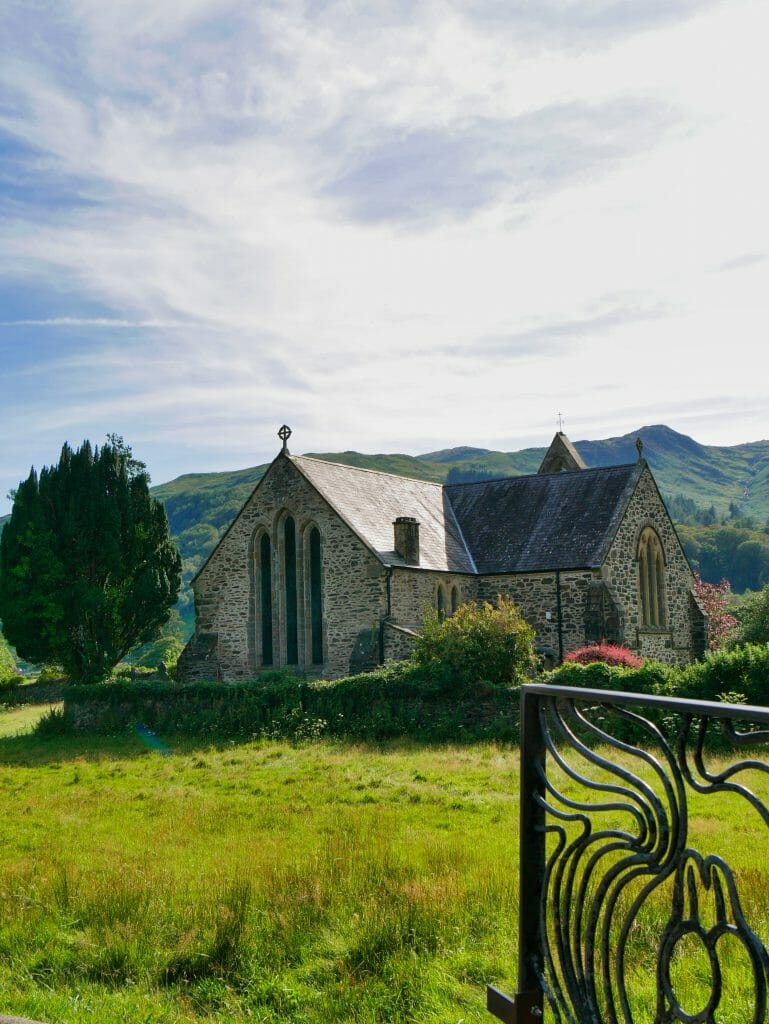 A church in Beddgelert Wales with hills behind