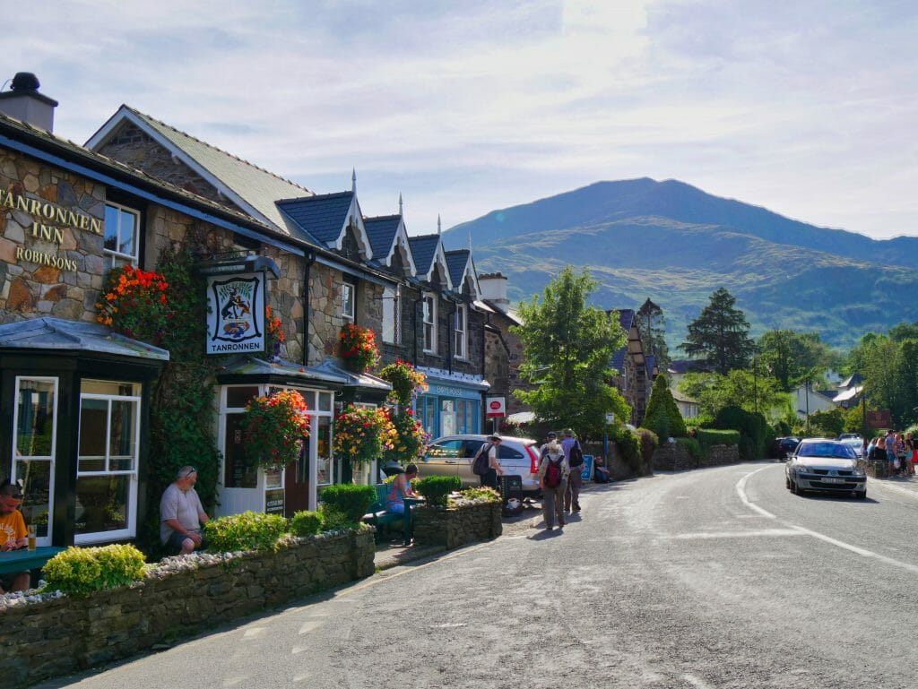 Things to do in Beddgelert Wales, stone shops on a street with hills behind