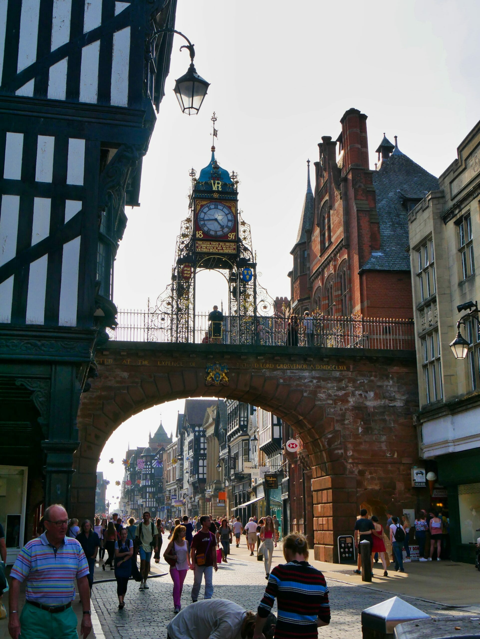Chester High Street with an old, ornate clock on top of a bridge