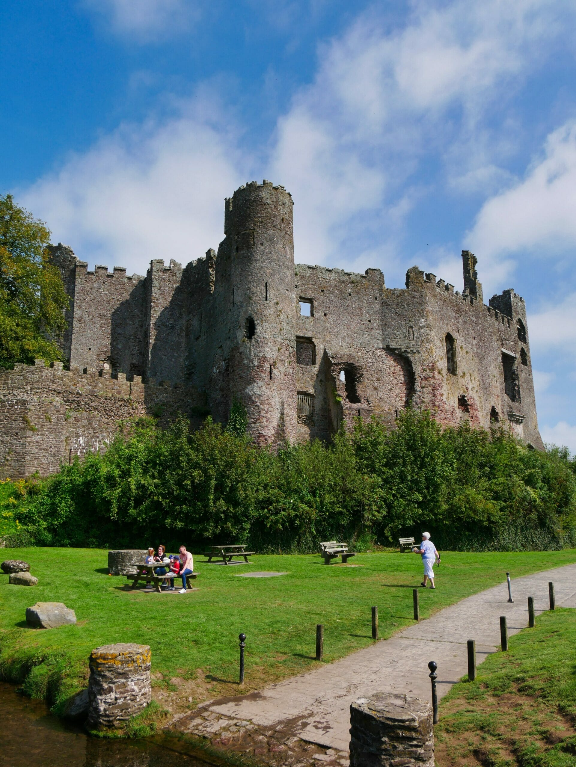 Laugharne castle Wales with people in front on the grass