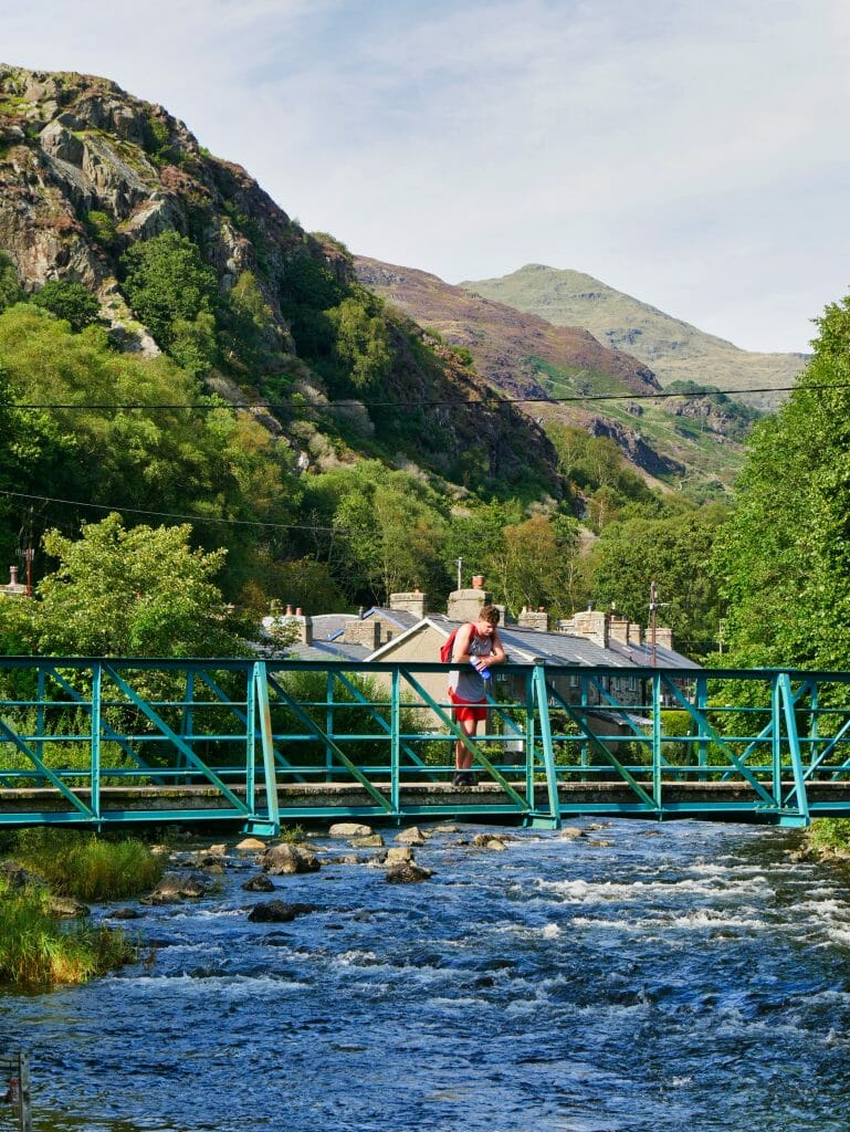 A man on bridge in Beddgelert Wales with a river flowing underneath and hills in the background