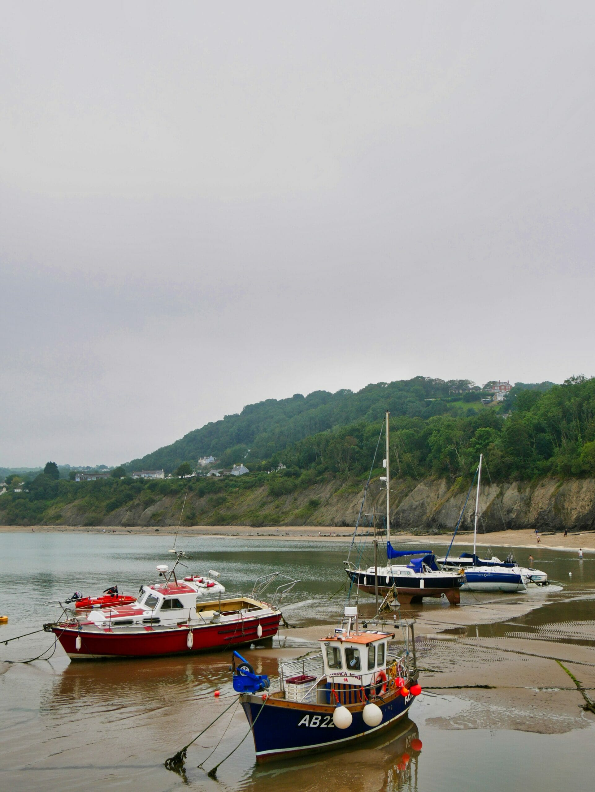 Some boats in the sandy water in New Quay in Wales