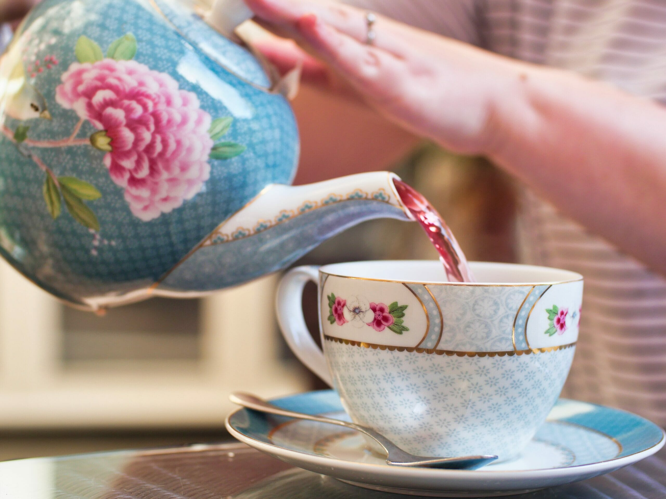 Kalyn pouring red berry tea from a floral tea pot in to a floral tea cup