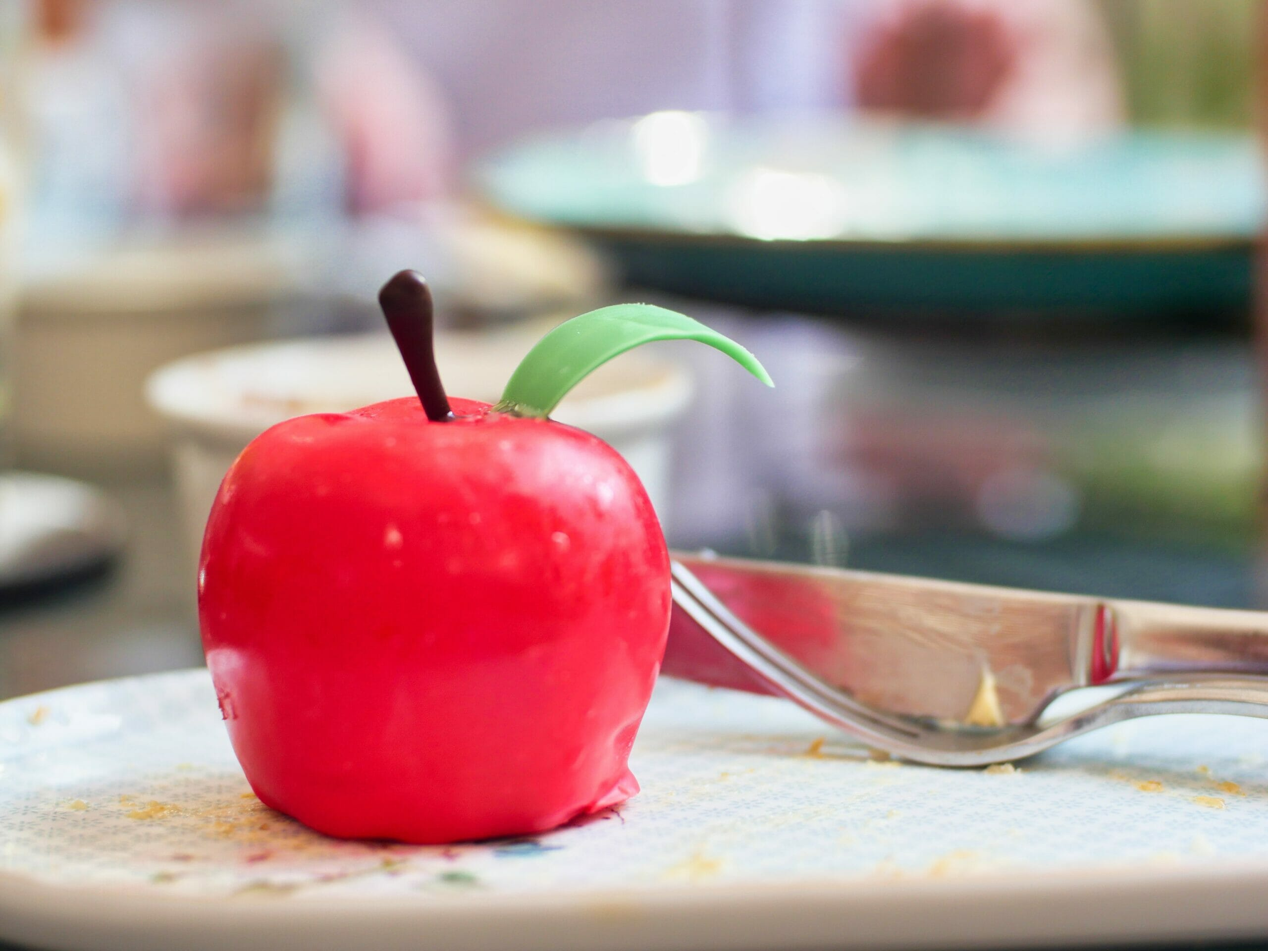 A dessert made to look like a red apple on a plate with a knife and fork