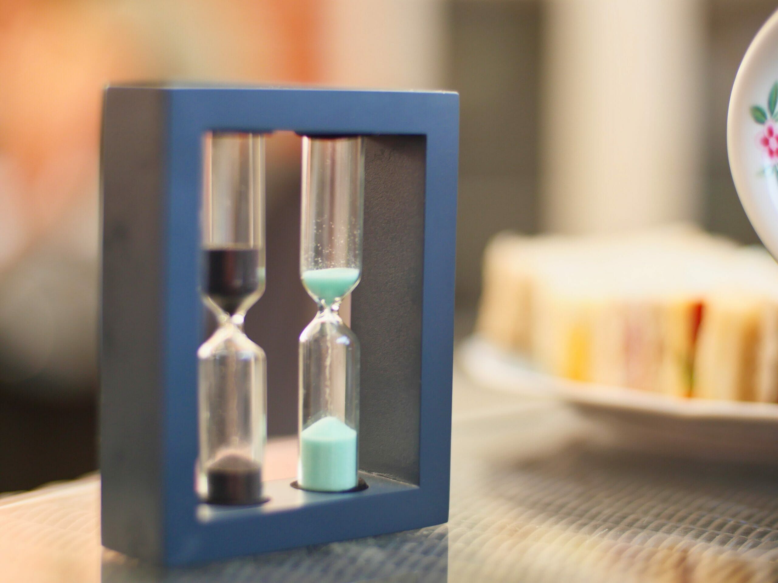 A tea timer with two sand timers, one with black sand and one with light blue sand