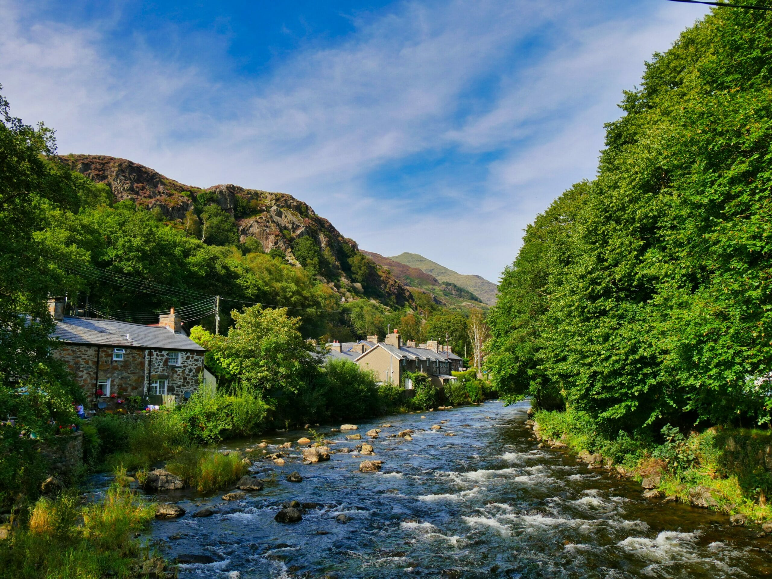 Stone cottages with river running past them and blue sky in Wales