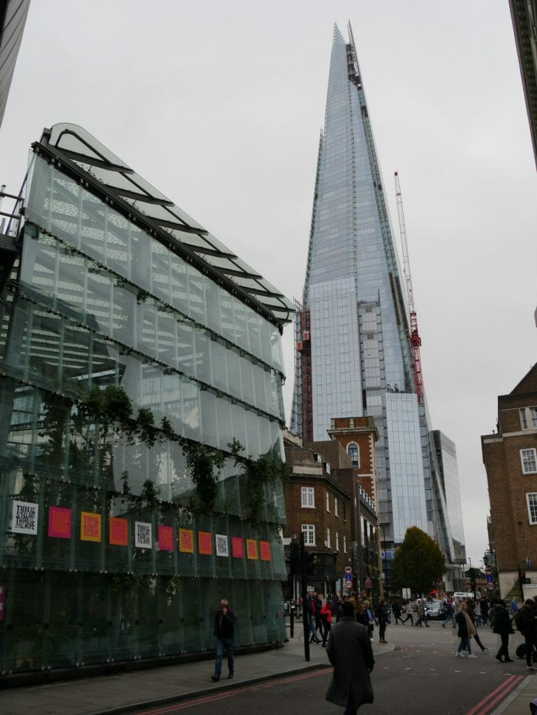 A glass building with The Shard in the background