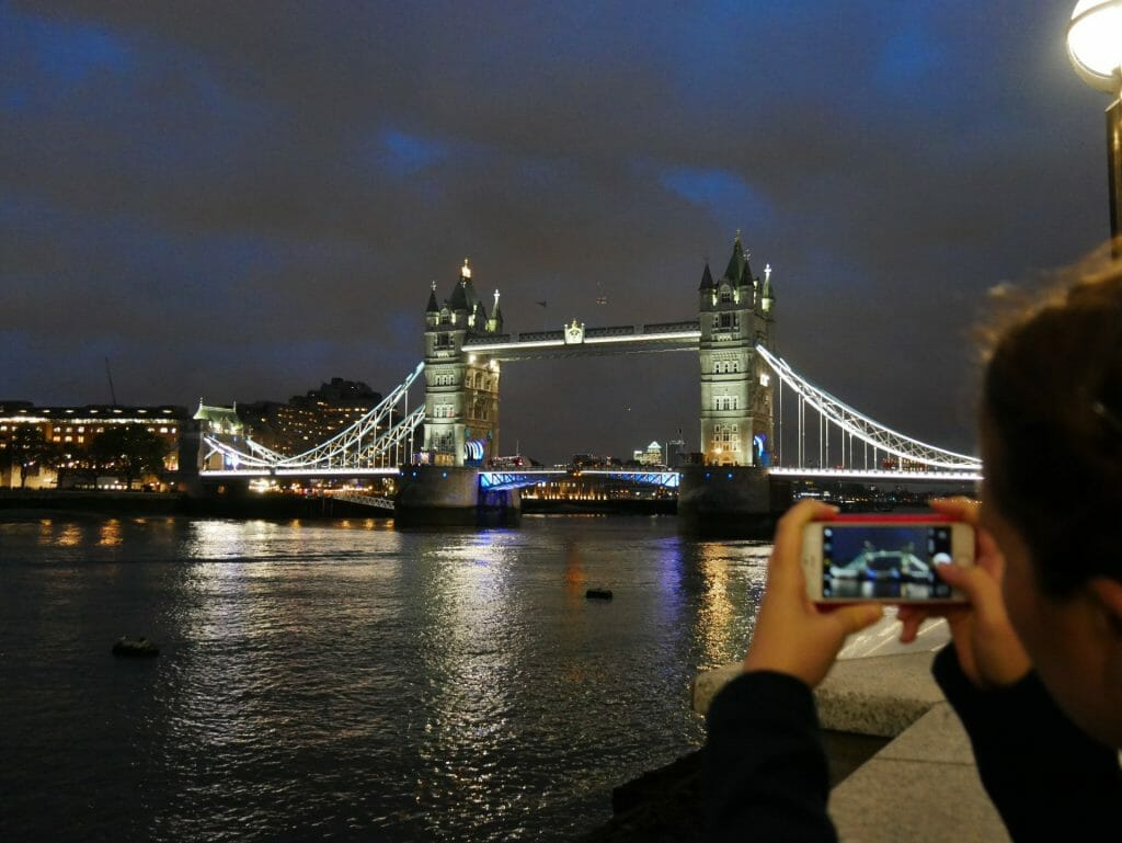 Kalyn taking a picture of Tower Bridge at night