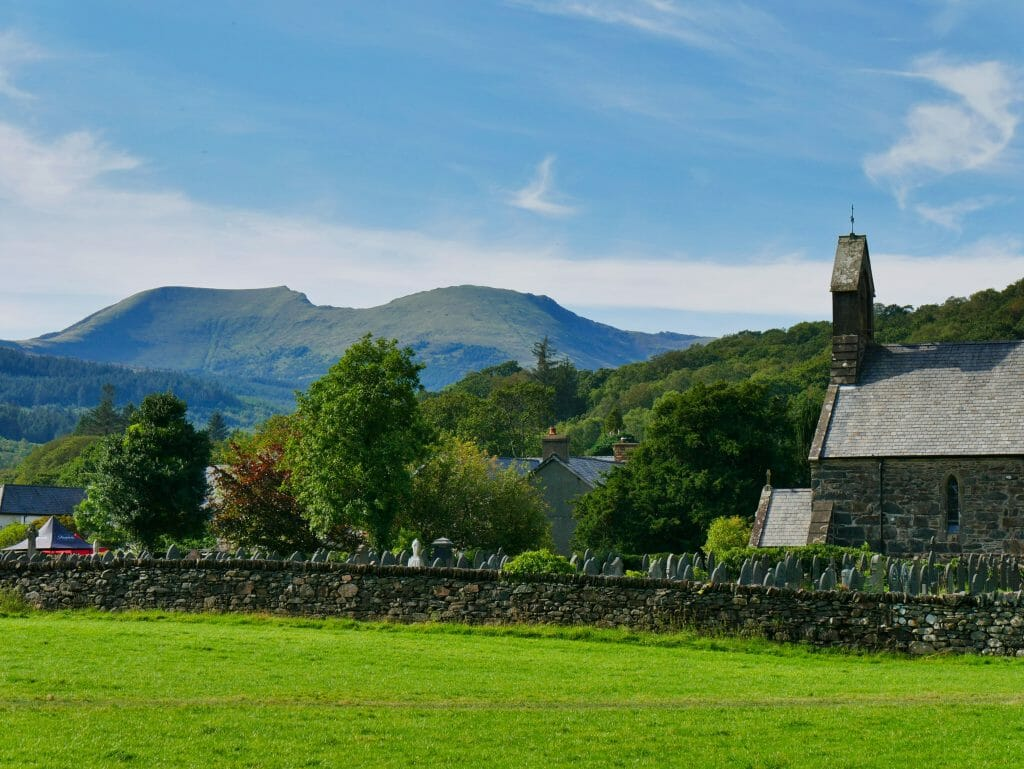 A field and church in Beddgelert, Wales, with a hill in the background