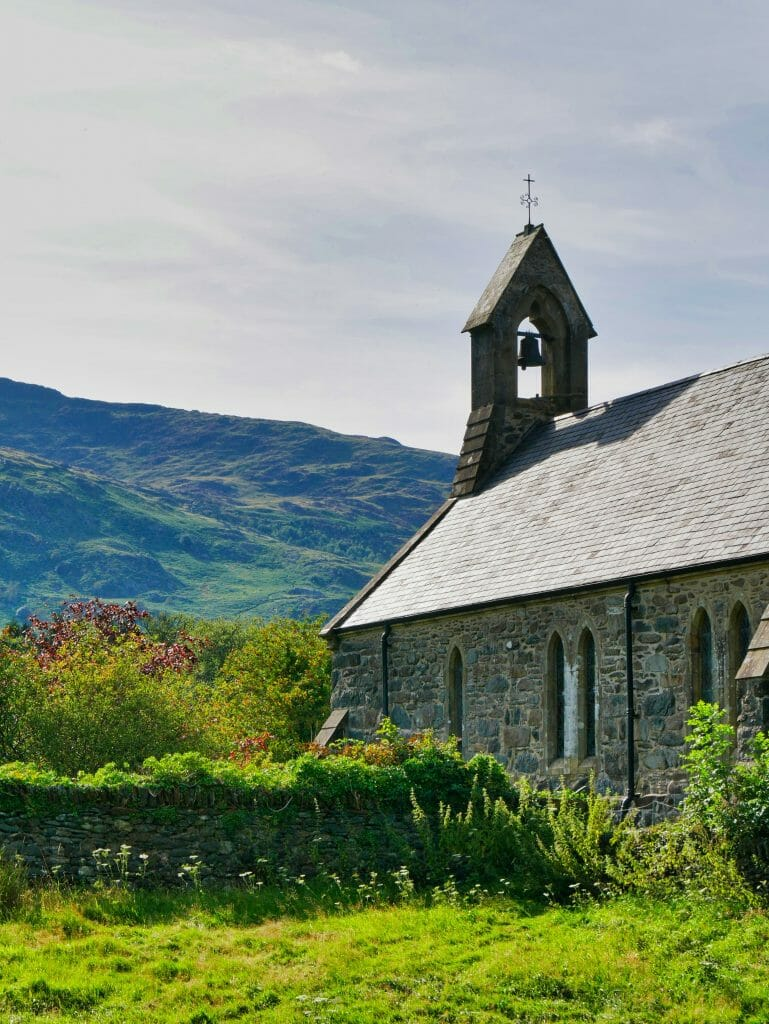 A church in Beddgelert, Wales, with a hill in the background