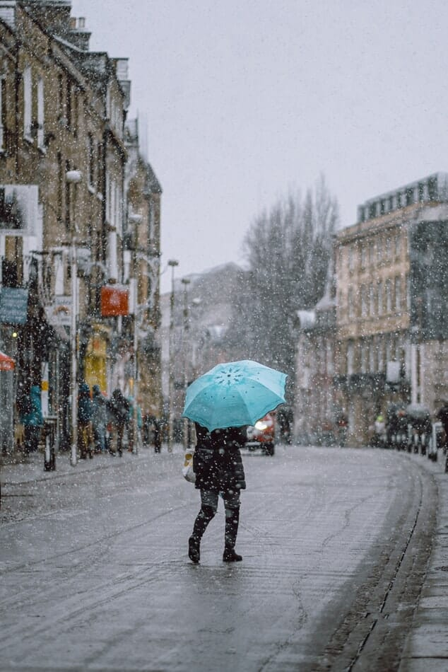 Person crossing the road in London as it snows, holding a blue umbrella