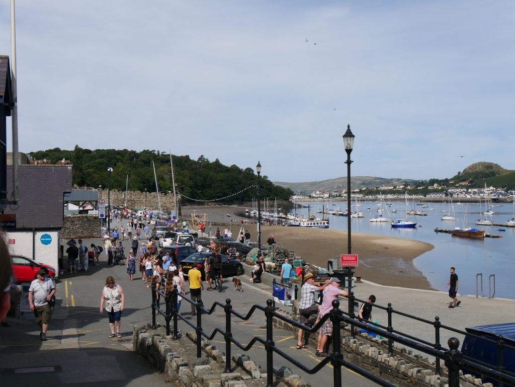 People looking out at boats in Conwy, North Wales