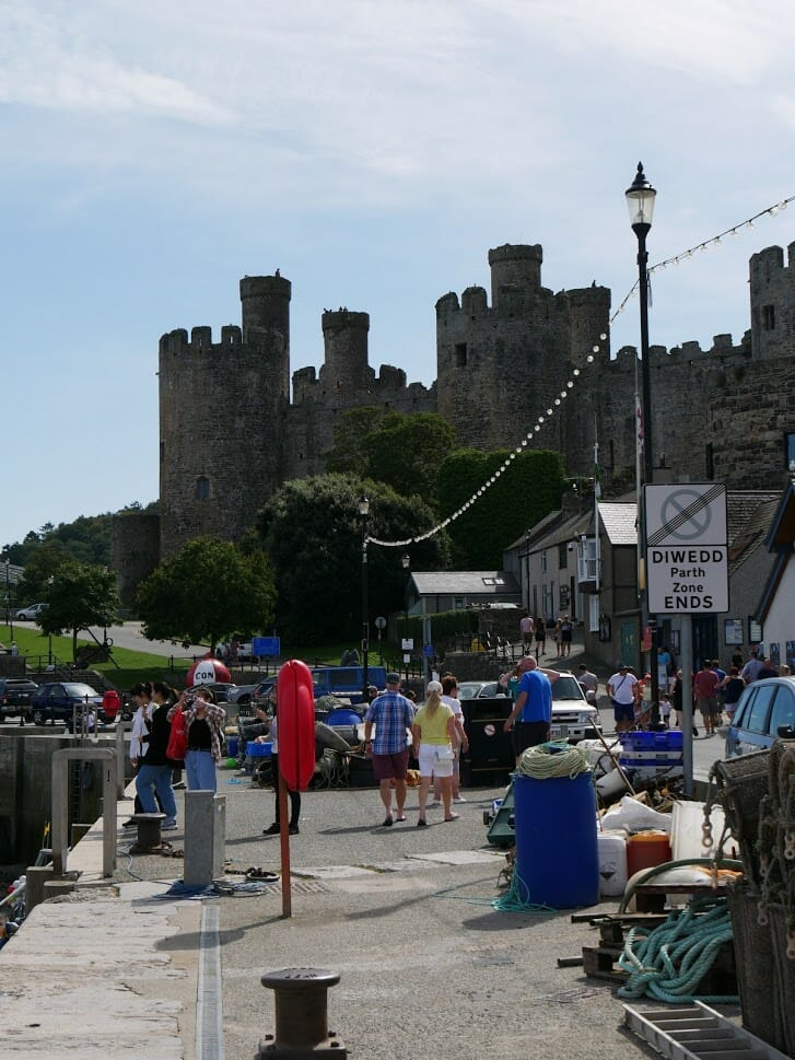 People walking along the street overlooked by the castle in Conwy, North Wales