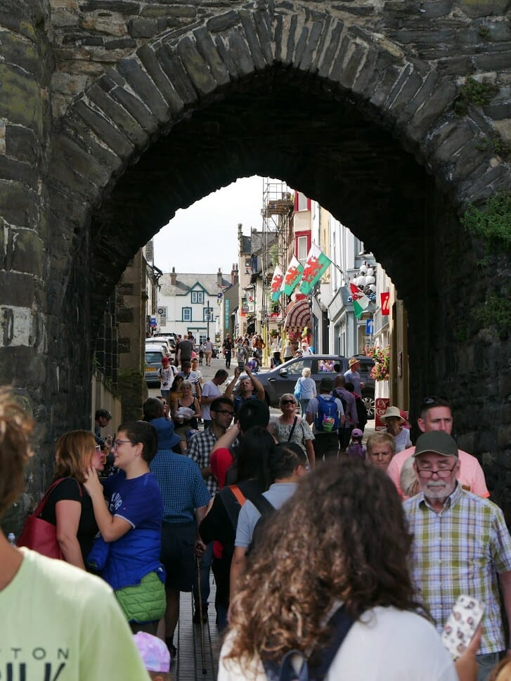 People walking under an old stone arch in Conwy