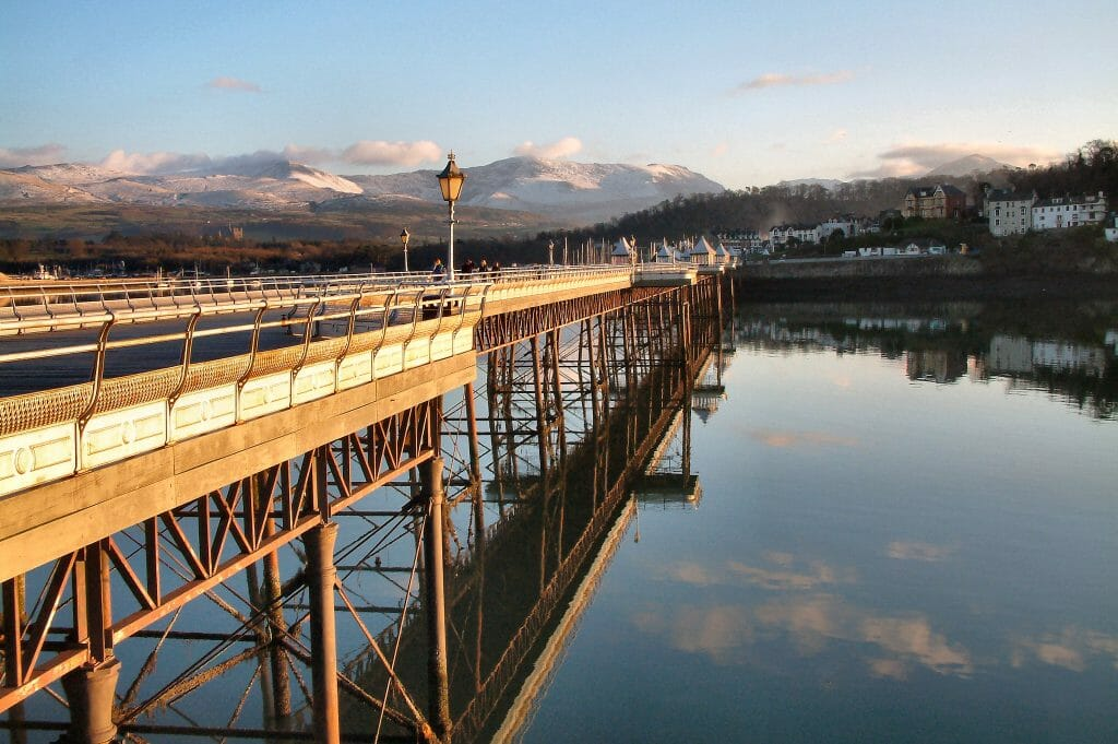Sunset over Garth Pier in Bangor, North Wales, with mountains in the background
