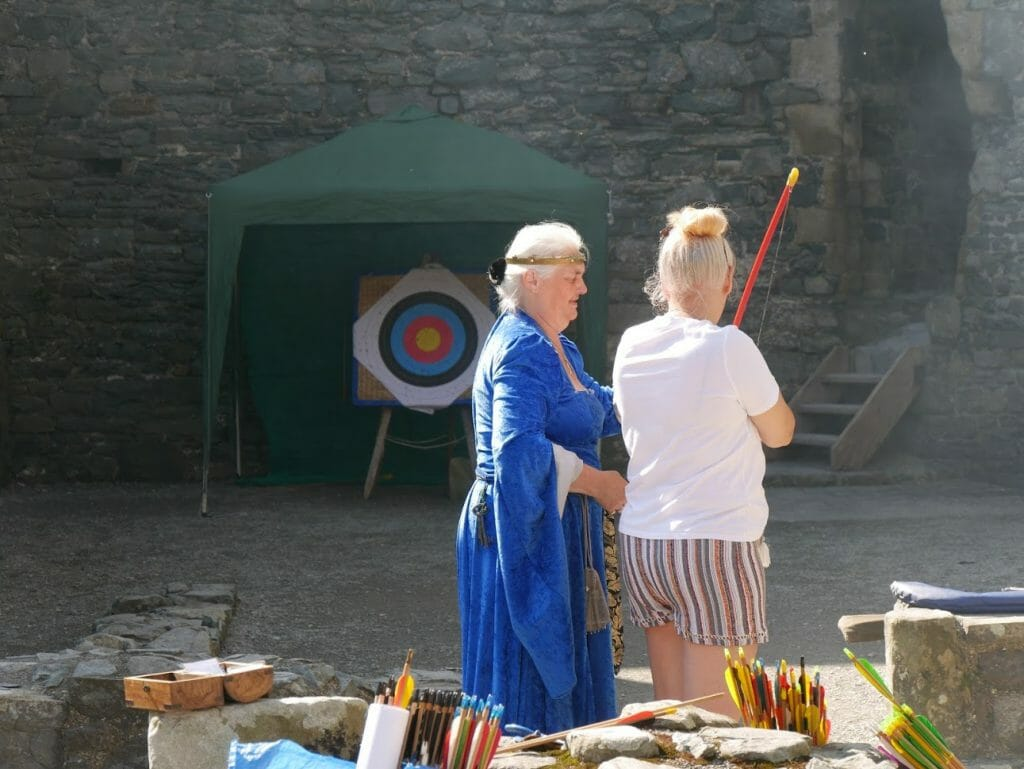 A lady learning to do archery in Harlech Castle in North Wales