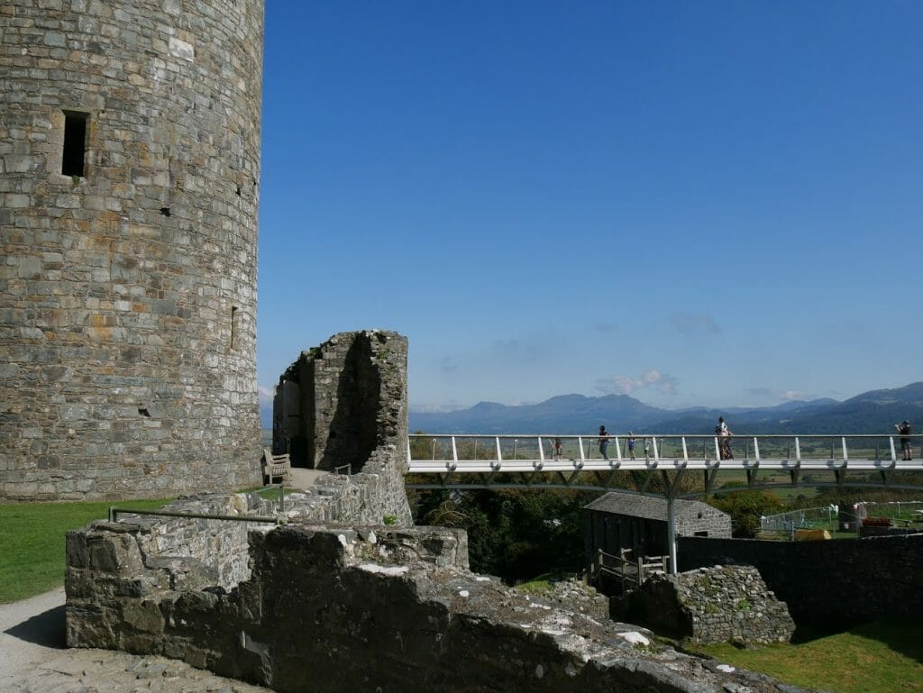 A bridge leading to Harlech Castle with mountains in the background