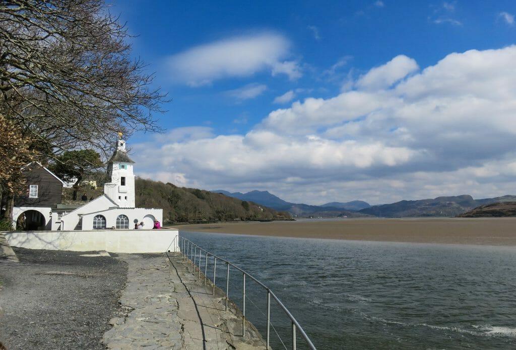 White building next to the water and sand at Portmeirion in North Wales
