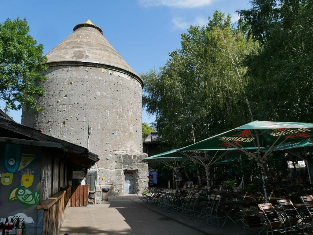 A stone silo with parasols in front of it in Berlin