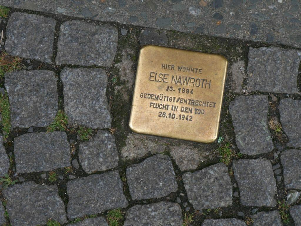 A golden memorial plaque in a cobbled sidewalk in Berlin