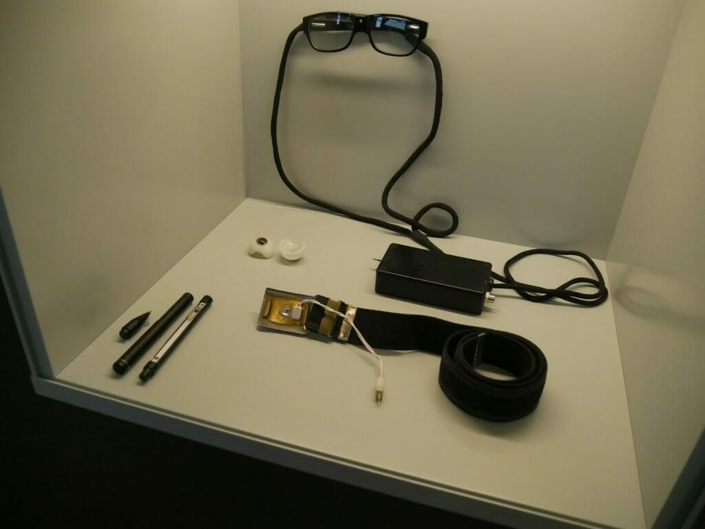 Some spy devices at the German Spy Museum, Berlin. A false eye, glasses with in-built camera, belt device, and pen device.