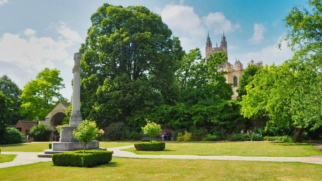 A green park with a view of Canterbury Cathedral in the background