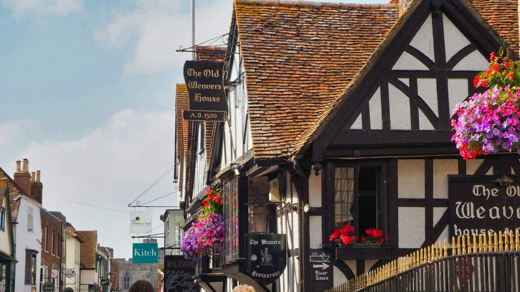 An old AD 1500 building with black wooden beams and restaurant signs on it in Canterbury