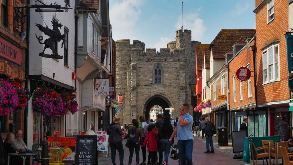 A street in Canterbury with people walking along and the medieval gates in the background