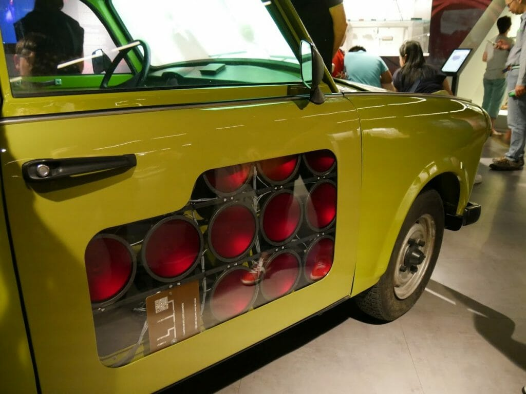 A mustard yellow Trabant car with infra-red lights built in to the passenger door at the German Spy Museum, Berlin