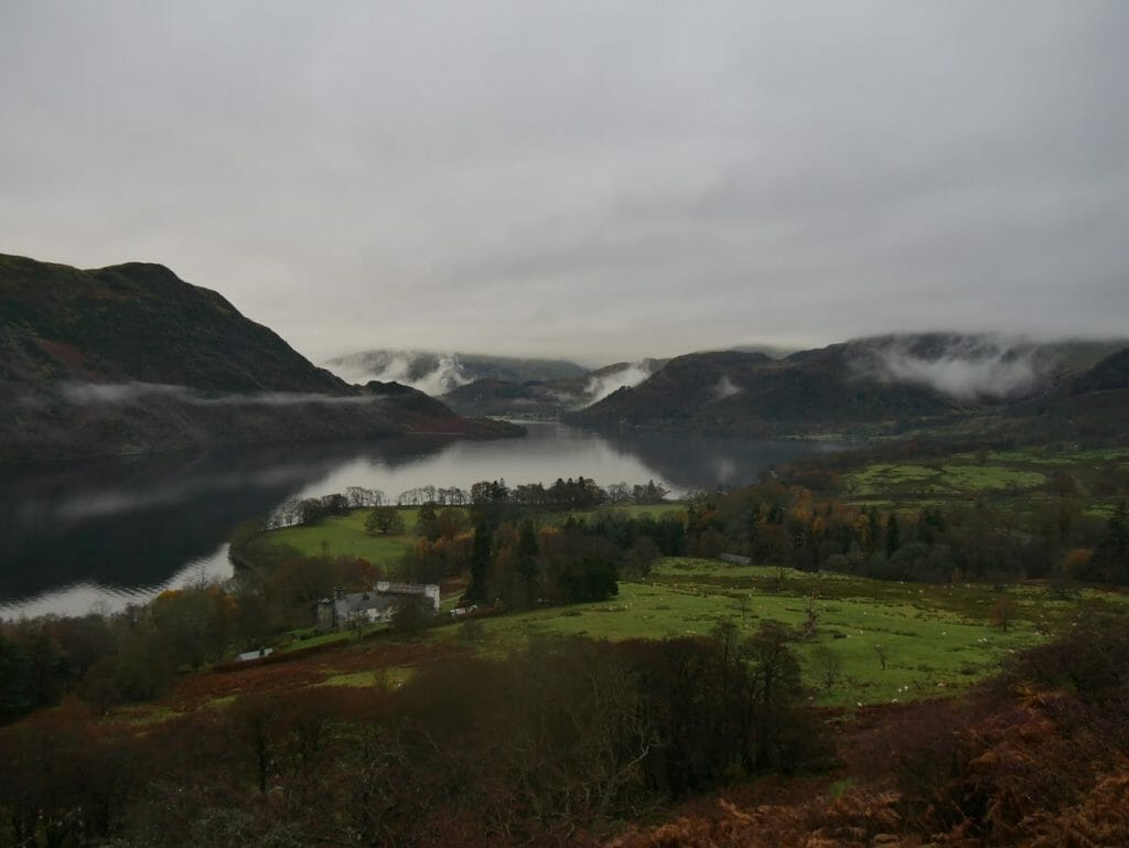 A view over Ullswater with cloudy skies and hills in the background