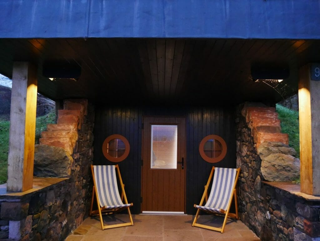 Deck chairs on the porch of a hobbit hole at The Quiet Site Ullswater