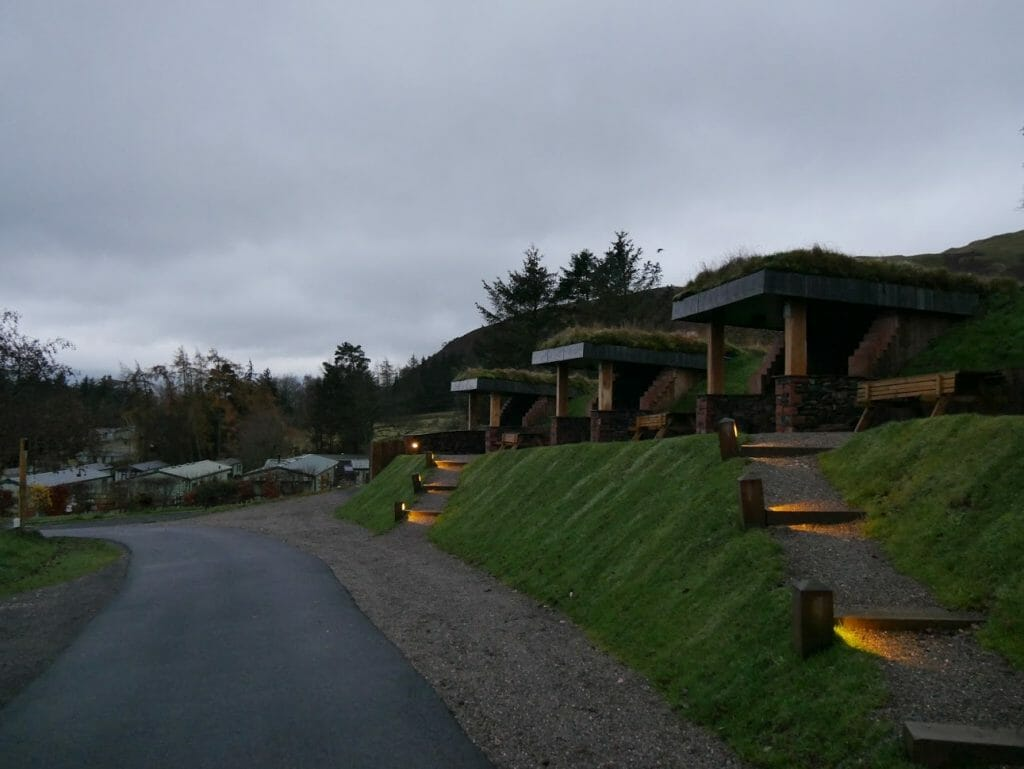 A line of hobbit holes on a grass ridge at The Quiet Site