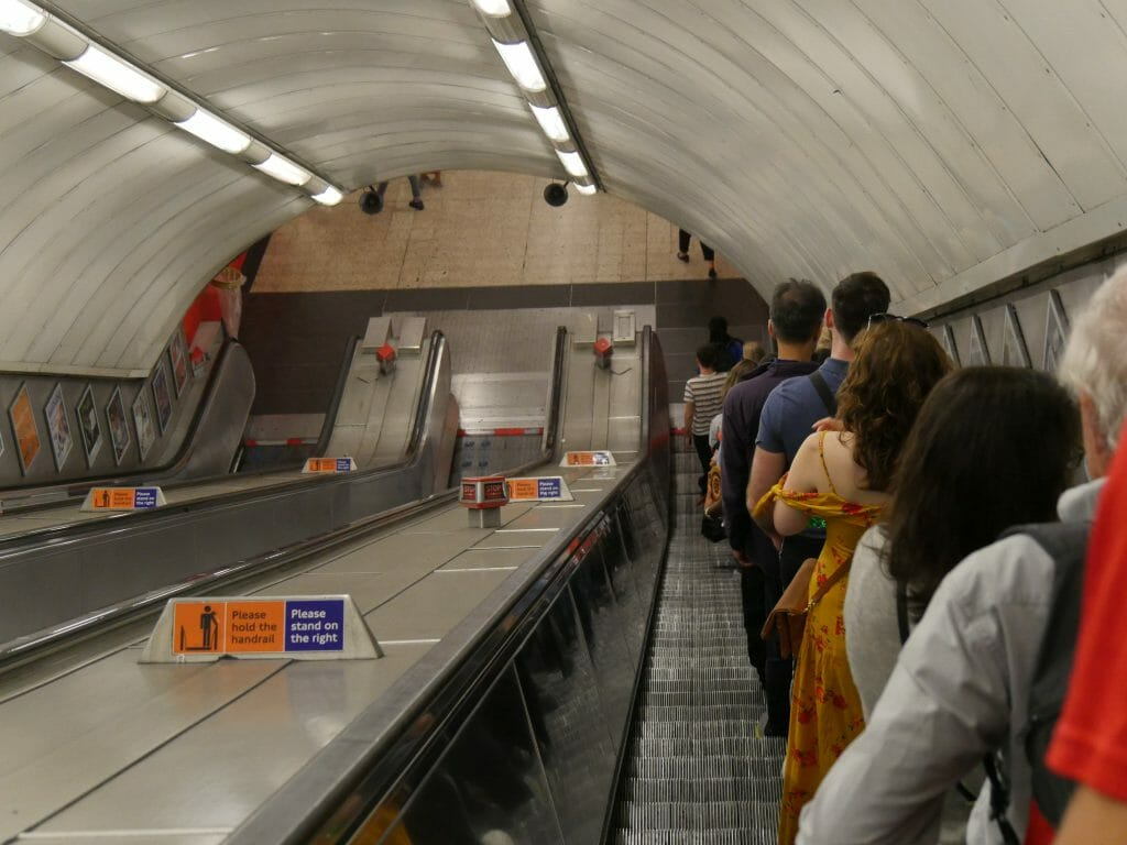 People standing on the right of an escalator on the tube underground in London