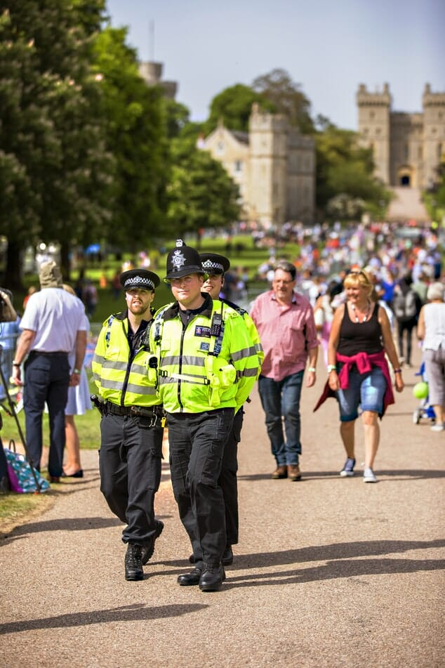 Police walking outside Windsor Castle with crows, in high-visibility jackets and no guns