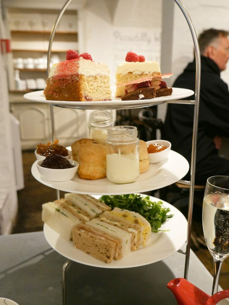 Afternoon tea sandwiches and cakes on a rack
