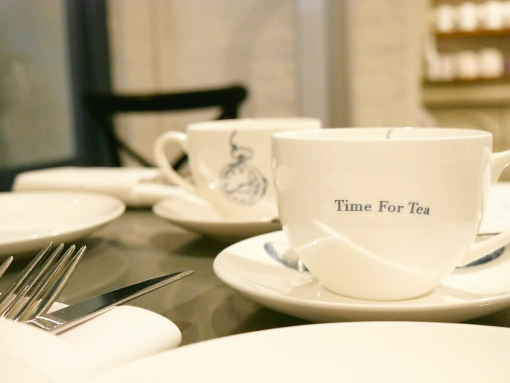 """A cup that says """"time for tea"""" on it"""